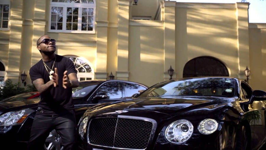 Davido seating next to a Bentley in a video location. He is one of the richest musicians in Nigerian | Constative.com