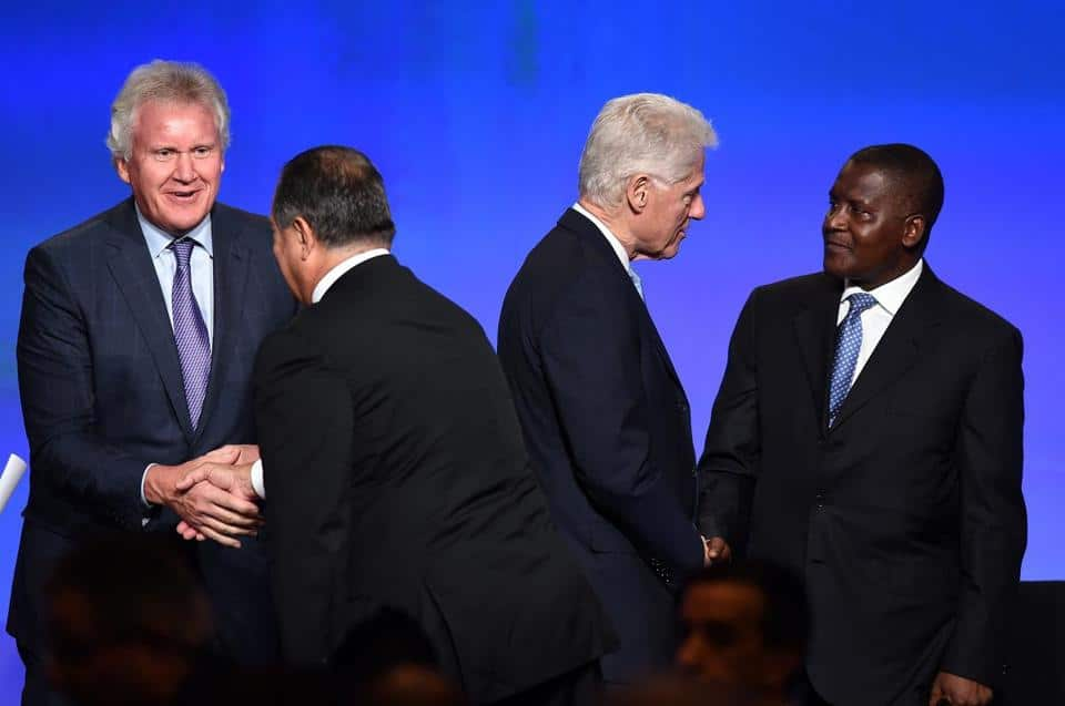 Aliko Dangote having a conversation with Bill Clinton at the US-Africa Business Forum, he is the richest back man with a net worth of $18.3billion | Photo credit: Afripol,org