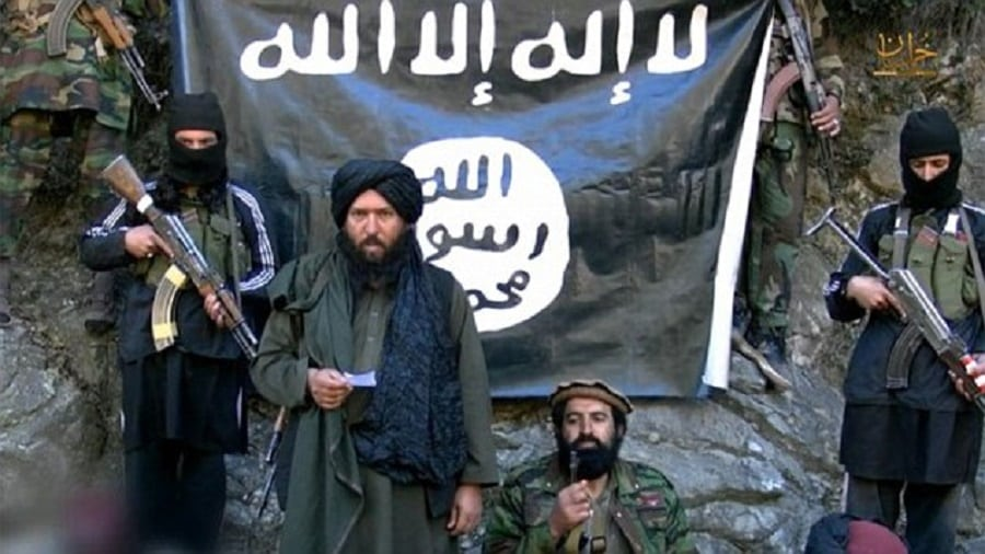 ISIS fighters pose in front of the Taliban's terror group's flag