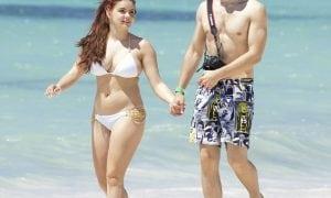 Ariel Winter and her boyfriend Laurent Gaudette walk hand in hand on the beach in the Bahamas