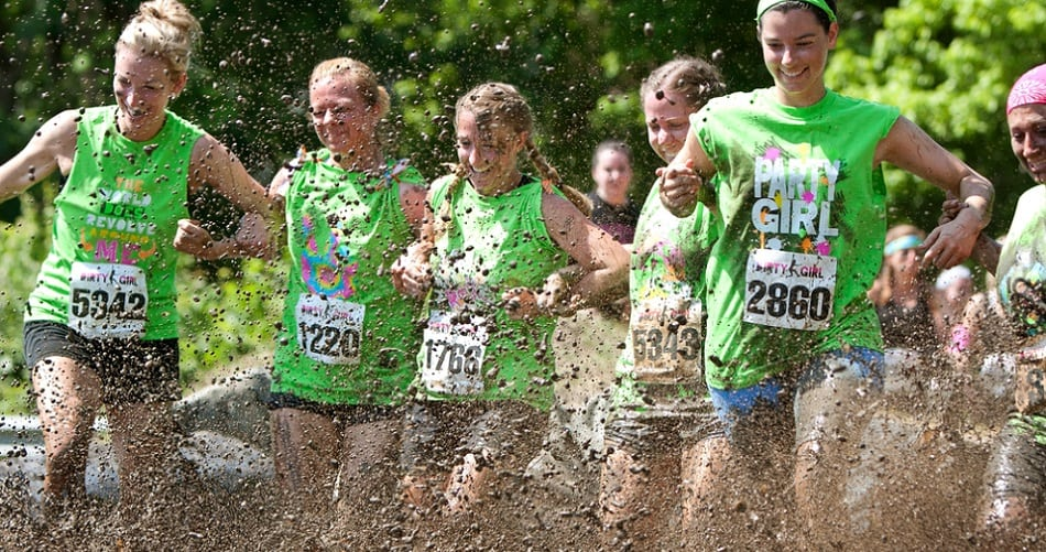 Young Women Stomp Through Mud Pit In Obstacle Course Run